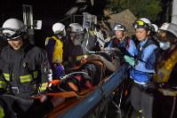 倒壊した家屋から救助した人を搬送する消防隊員ら=熊本県益城町で2016年4月15日午前0時38分、和田大典撮影