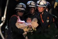 倒壊した家屋から女児を救出する警察官ら=熊本県益城町で2016年4月15日午前3時44分、和田大典撮影