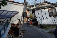 地震で倒壊した建物の脇を歩く人たち=熊本県益城町で2016年4月15日午前7時15分、津村豊和撮影