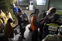 益城町役場から自衛隊の車両で避難所となる体育館に運ばれる住民たち=熊本県益城町で2016年4月15日午前4時29分、津村豊和撮影