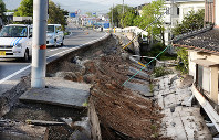 地震で土手が大きく崩れた道路=熊本県益城町で2016年4月15日午前7時22分、津村豊和撮影