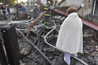 地震による火災で自宅を焼失し、立ち尽くす女性=熊本県益城町で2016年4月15日午前6時、和田大典撮影