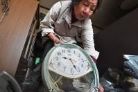 地震で落ちて、発生時刻で止まった時計を片付ける女性=熊本県益城町で2016年4月15日午前8時28分、和田大典撮影