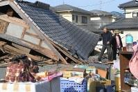 地震で倒壊した自宅の片付けをする一家=熊本県益城町で2016年4月15日午前7時53分、和田大典撮影
