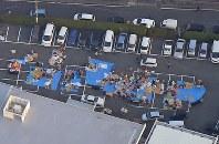 地震で町役場の駐車場にビニールシートを広げ、避難している人たち=熊本県益城町で2016年4月15日午前6時22分、本社ヘリから矢頭智剛撮影