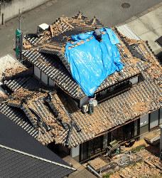 地震で瓦が落ちた家屋の屋根にブルーシートを張る人たち=熊本県益城町で2016年4月15日午前11時40分、本社ヘリから幾島健太郎撮影