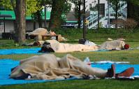 ビニールシートの上で毛布にくるまって一晩を過ごした人たち=熊本市中央区の白川公園で2016年4月15日午前6時20分、中里顕撮影