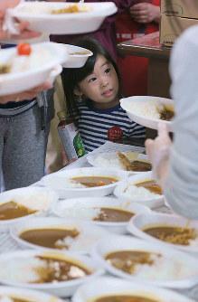 炊き出しのカレーライスを見つめて笑顔を見せる女の子=熊本県益城町で2016年4月15日午後6時18分、宮武祐希撮影