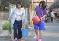 川から水を運ぶ人たち=熊本県益城町で2016年4月15日午後5時58分、和田大典撮影