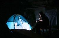 倒壊した家屋の前でテントを張って夕食の弁当を食べる被災者=熊本県益城町で2016年4月15日午後8時3分、宮武祐希撮影