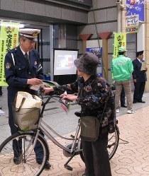 買い物客にチラシを配って事故防止・犯罪防止などを呼びかける飯塚署員ら