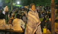An earthquake evacuee wrapped in a blanket stands in Shirakawa Park, in Mashiki, Kumamoto Prefecture, in the pre-dawn hours of April 16, 2016. (Mainichi)