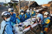A man is carried on a stretcher after being rescued from a collapsed house, in Mashiki, Kumamoto Prefecture, at 6:27 a.m. on April 16, 2016. (Mainichi)