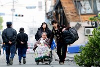 An elderly man in a wheelchair is pushed by his grandchildren along a cracked and debris-strewn road to an evacuation shelter, in Mashiki, Kumamoto Prefecture, on April 16, 2016. (Mainichi)