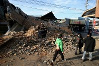 People walk by a home that newly collapsed from temblors continuing since the wee hours of April 16 in Mashiki, Kumamoto Prefecture, on April 16, 2016. (Mainichi)
