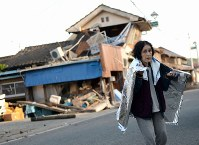 A woman is seen in front of a badly damaged home, in Mashiki, Kumamoto Prefecture, on April 16, 2016. (Mainichi)