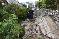 A woman walks along a pathway by a collapsed wall, in Mashiki, Kumamoto Prefecture, on April 16, 2016. (Mainichi)