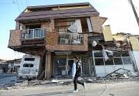 A man carrying a tarp he received at the town hall walks in front of a badly damaged house, in Mashiki, Kumamoto Prefecture, on April 16, 2016. (Mainichi)