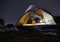 A couple that could not stay in an evacuation shelter because they have three dogs, camps in front of their house, in Mashiki, Kumamoto Prefecture, on April 15, 2016. (Mainichi)
