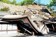 Kumamoto Daijingu shrine is seen crushed by a collapsed stone wall, in Chuo Ward, Kumamoto, on April 16, 2016. (Mainichi)
