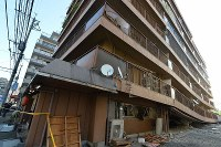 An apartment building with a largely collapsed first floor is seen, in Nishi Ward, Kumamoto, on April 16, 2016. (Mainichi)