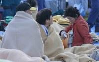 町役場前で毛布にくるまりながら夜を明かした避難者たち=熊本県益城町で2016年4月16日午前6時16分、宮武祐希撮影