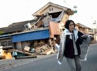 毛布にくるまり、倒壊した家屋の前を歩く女性=熊本県益城町で2016年4月16日午前7時11分、久保玲撮影