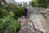 地震で崩れた壁が散乱する道を歩く女性=熊本県益城町で2016年4月16日午前6時7分、久保玲撮影