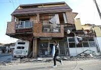 倒壊した家屋の前を役場から配布されたブルーシートを持って歩く男性=熊本県益城町で2016年4月16日午前6時54分、久保玲撮影
