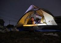 犬を3匹飼っているため避難所に行けず、自宅前の広場にテントを張って過ごす夫婦=熊本県益城町で2016年4月15日午後7時48分、久保玲撮影