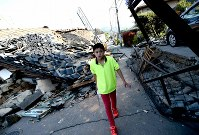 水を入れたペットボトルを持って倒壊した家屋の側を歩く一丸由喜さん(12)。水道が復旧していないため、水を求め被害を受けた祖父母宅と公園を何度も往復した=熊本県益城町で2016年4月15日午後4時59分、久保玲撮影