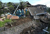 倒壊した家屋で捜索する救急隊員ら=熊本県益城町で2016年4月16日午前7時47分、久保玲撮影