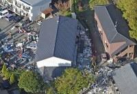 救助活動が続く東海大阿蘇キャンパスそばのアパート(中央)=熊本県南阿蘇村で2016年4月16日午前7時29分、本社ヘリから矢頭智剛撮影