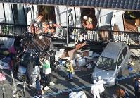 1階部分が押し潰されたアパートの2階部分で続けられる救助活動=熊本県南阿蘇村で2016年4月16日午前7時29分、本社ヘリから矢頭智剛撮影