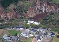 救助活動が続く「グルーンハイツ」(中央)。周辺は大規模な土砂崩れが起きている=熊本県南阿蘇村で2016年4月16日午前9時28分、本社機「希望」から梅村直承撮影