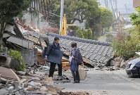未明の大きな揺れで家屋が倒壊し、生活用品を持ち出す親子=熊本県益城町で2016年4月16日午前9時36分、三村政司撮影