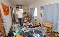 部屋が傾いて、家具などが散乱した集合住宅に戻りぼうぜんとする男性=熊本県益城町で2016年4月15日午後3時17分、三村政司撮影