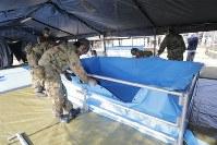 避難所の庭に仮設の風呂場を作る自衛隊員=熊本県益城町で2016年4月15日午後4時13分、三村政司撮影