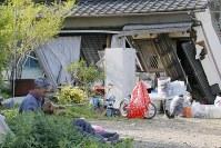 倒壊した自宅の前で座り込む男性。犬は昼過ぎにようやく助け出したという=熊本県益城町で2016年4月15日午後4時、三村政司撮影