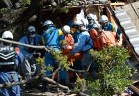 倒壊した家屋から救助される女性=熊本県益城町で2016年4月16日午前8時45分、久保玲撮影