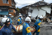 A university student found in cardiopulmonary arrest is carried away from a collapsed two-story apartment building in Minamiaso, Kumamoto Prefecture, on April 16, 2016. The student was later confirmed dead. (Mainichi)