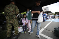 A local resident receives a bag of cooked rice at a distribution center in Mashiki, Kumamoto Prefecture, on Saturday, April 16, 2016. (AP Photo/Koji Ueda)