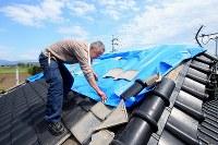 降雨に備え、地震で壊れた屋根をブルーシートで覆う古閑公博さんは「あんな大きな地震が来たらまた直さなくちゃいけない」とため息をついた=熊本県益城町で2016年4月16日午後2時12分、森田剛史撮影