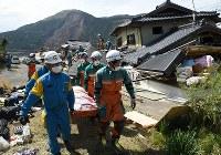 地震で倒壊した家屋から女性を搬送する警察官。奥は大規模崩落が起きた山肌=熊本県南阿蘇村で2016年4月16日午後2時36分、丸山博撮影