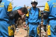 倒壊した家で、母親の島崎京子さんの遺体を確認し、涙をぬぐいながら警察官にお礼を言う浩さん熊本県益城町で2016年4月16日午前10時35分、和田大典撮影