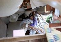 避難所で使うため倒壊した自宅から毛布を運ぶ男性=熊本県西原村で2016年4月16日午後4時56分、久保玲撮影