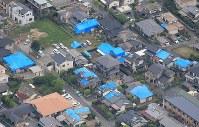 雨に備えて青いビニールシートが架けられた屋根=熊本県益城町で2016年4月16日午後4時33分、本社機「希望」から梅村直承撮影