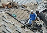 倒壊した家屋の中をビニールシートを持って歩く女性=熊本県益城町で2016年4月16日午前9時57分、久保玲撮影