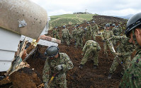 Self-Defense Force members search for the missing at the site of a landslide, in Minamiaso, Kumamoto Prefecture, on April 17, 2016. The white building in the background is Kyoto University's Aso Volcanological Laboratory. (Mainichi)