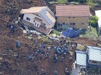 地震で発生した土砂崩れで押しつぶされた高野台団地の民家周辺で行われる捜索活動=熊本県南阿蘇村で2016年4月17日午後0時54分、本社機「希望」から梅村直承撮影